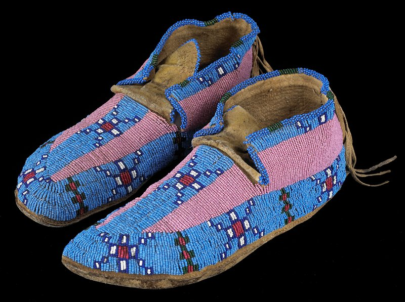uppers beaded overall with background panels of blue and pink, and geometric square designs; large plain tongues, trimmed in blue beads; fringe on heels