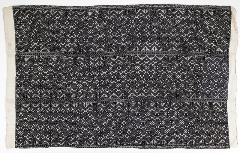 """three vertical panels; overall embroidery using indigo wool on a natural colored cotton ground; design of diamond shapes and zigzag designs separated by smaller zigzag borders; covered with pattern; 3"""" natural border at top and bottom; hand sewn hem"""