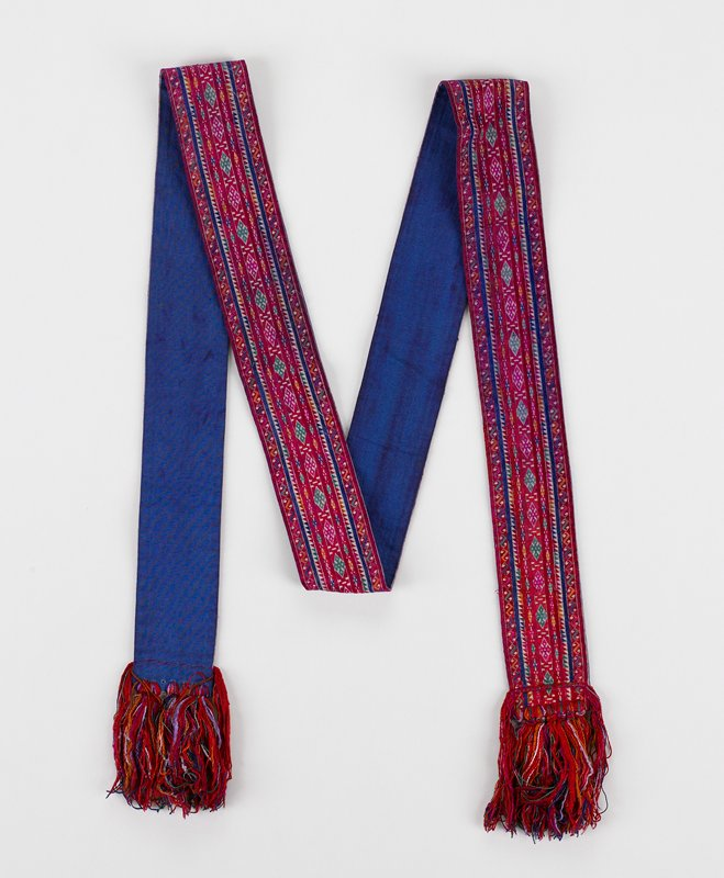 """red, blue satin stitch embroidery in narrow-band patterns of diamonds, scrolls, triangles with some green and yellow; 3"""" multicolored fringe at each end; lined in bright blue cotton"""
