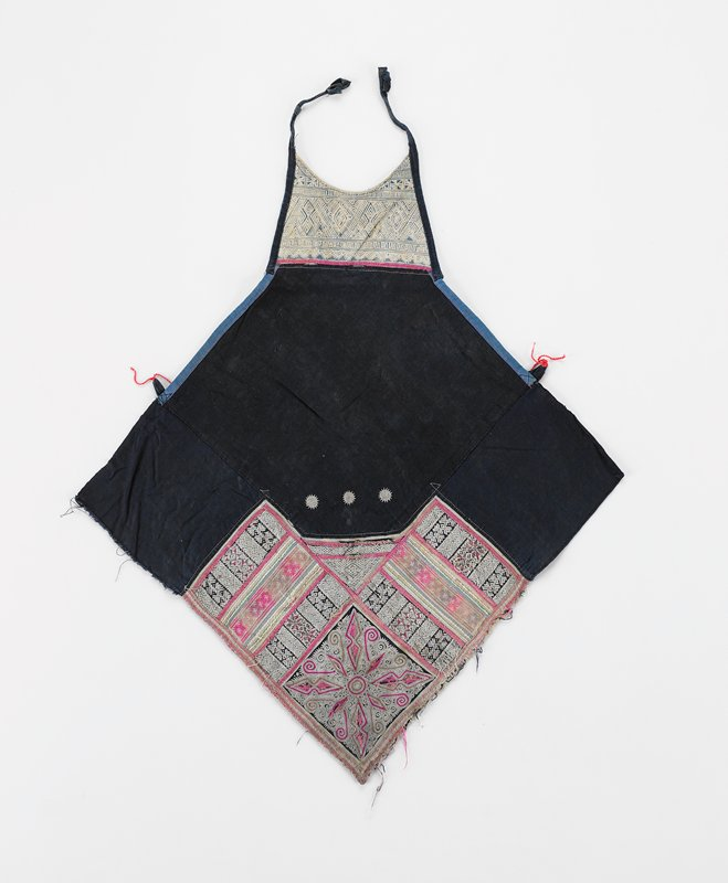 """worn pounded indigo diamond shape apron; added batik bib with 2 ties; lower third has sections of geometric embroidery and tape in pink, red and white; applique divided by 3/8"""" red tape; bottom side edges bound with silver and red metallic tape; three 1/2"""" embroidered medallions at middle of apron; two 1/2"""" side loops tied with red string"""
