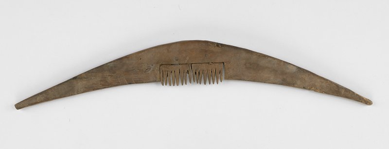a: braided cotton tie with corn husk-type tassel; b: piece of hand-carved wood, slightly bowed; two hand carved combs attached to center; c-f: multiply strands of twisted hair--some strands knotted throughout; c has 7 hanks attached at top; d has 3 hanks; e and f each have one hank