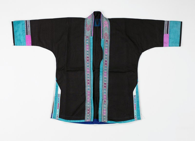 pounded black and turquoise silk band with applied embroidery; band of geometric embroidery in turquoise, pink, dark rust and white on front; turquoise silk band front, back and vents; vents have narrow embroidery inset; sleeve cuffs of turquoise silk with pink and embroidery; inset neck band wide geometric embroidery diamond shaped in same colors; pounded indigo