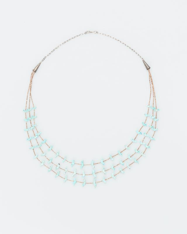 Zuni fetish necklace; triple strands dark brown shell beads with 66 carved turquoise birds; strung on string below silver horns, silver loops and clasp above