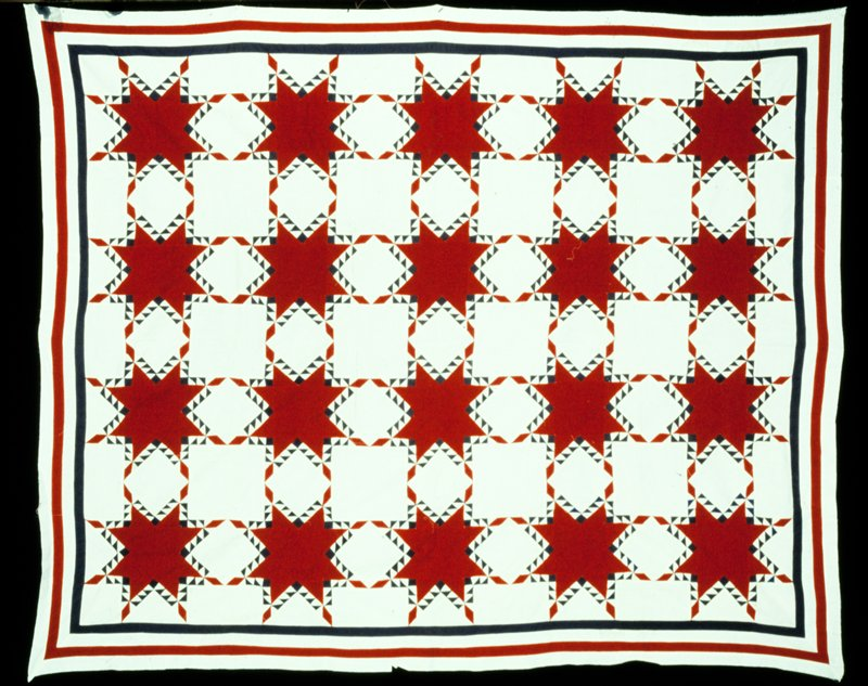 red 8-pointed stars with blue triangle appliqué pattern on natural light ground