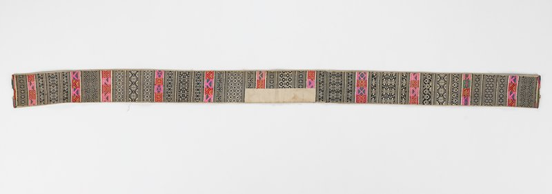 off-white long band with rows of black and white embroidered geometric patterns with accenting rows of red, pink, green and yellow geometric bands; lined in off-white
