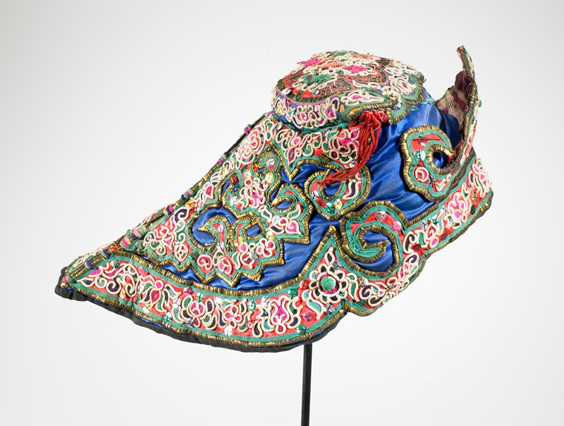 "white, red, green; royal blue satin base completely covered with appliqued floral and leaf designs using sequins; small, round, white braid in curly designs; yellow and white metal outlines designs; multicolored sequins; ""horns"" on either side with fringe; red on one side, yellow on the other; stiff, crown-like piece in front; back tapers down to a point (helmet shape?); very similar to 2004.67.370; quilted lining"