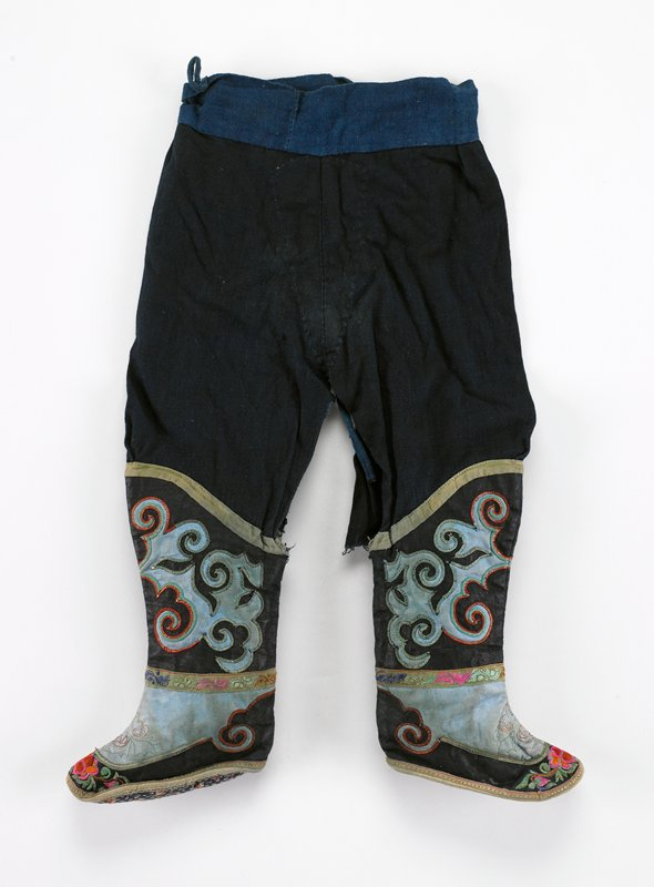 indigo pants with attached boots; black, blue; applique outlined with stitched metal; plain and floral bands frame design; feet also appliqued in black with some floral embroidery at toe; floral fabric soles; ties at waistband