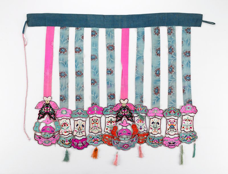 blues, pinks; ten individual streamers attached to a wide blue waistband that ties with a cord; eight streamers have blue print cloth, two plain pink; blue streamers end with three large, stiff embroidered cutouts; pink streamers have more elaborate cutouts including some metal discs; all streamer cutouts are figures and/or floral designs joined with metal beads edged with thin braid--some end in tassels; one metal bell (?) on one tassel