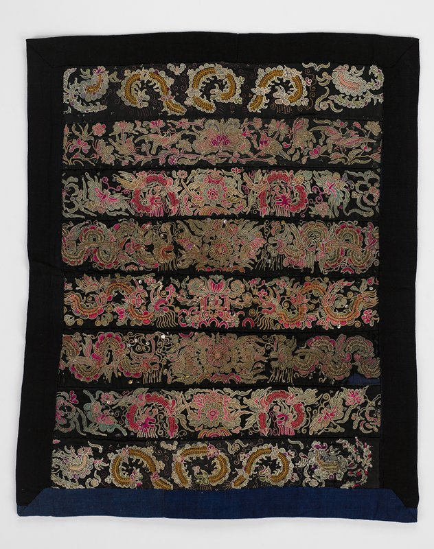 lined panel; black with 8 dull multi-colored horizontal joined embroidered bands of flora and fauna; scattered metal disks; black border top and sides, blue border at bottom; lined in dark blue indigo cotton