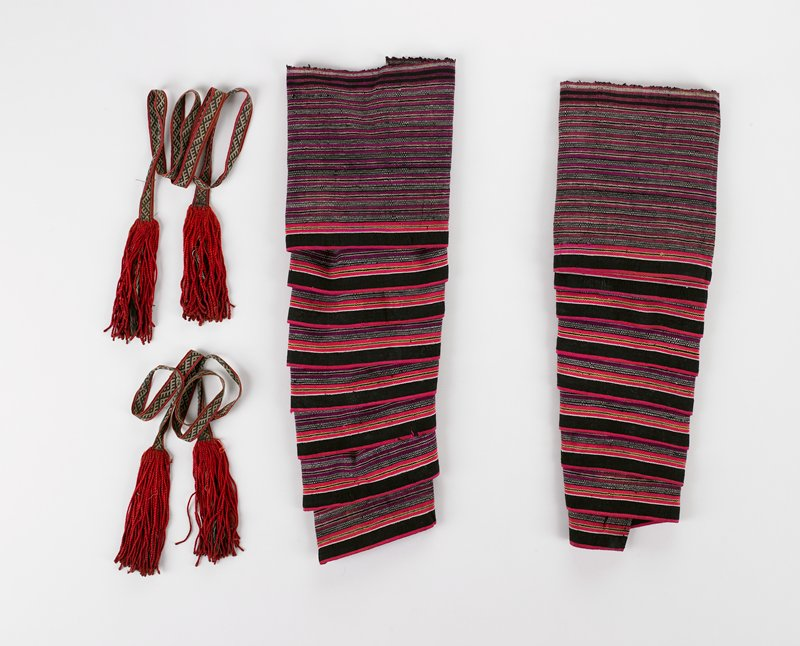 pair of long, wide, woven striped horizontal bands in black, red, white, gold and magenta; pair of narrow woven ties with attached tassels in black, white and red