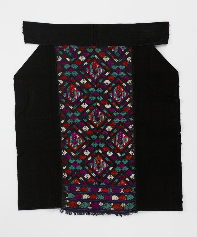 black with red, purple, green, white; two solid black side panels with center fringed panel of satin stitch embroidery, geometrics and animals; wide black waistband