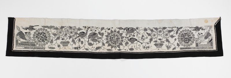 black border on sides and bottom; black embroidery on off-white fabric; pattern has guard dogs on either end and three large patterned circles, with flowers and birds intersperced; PL upper corner edge has five Chinese (?) characters