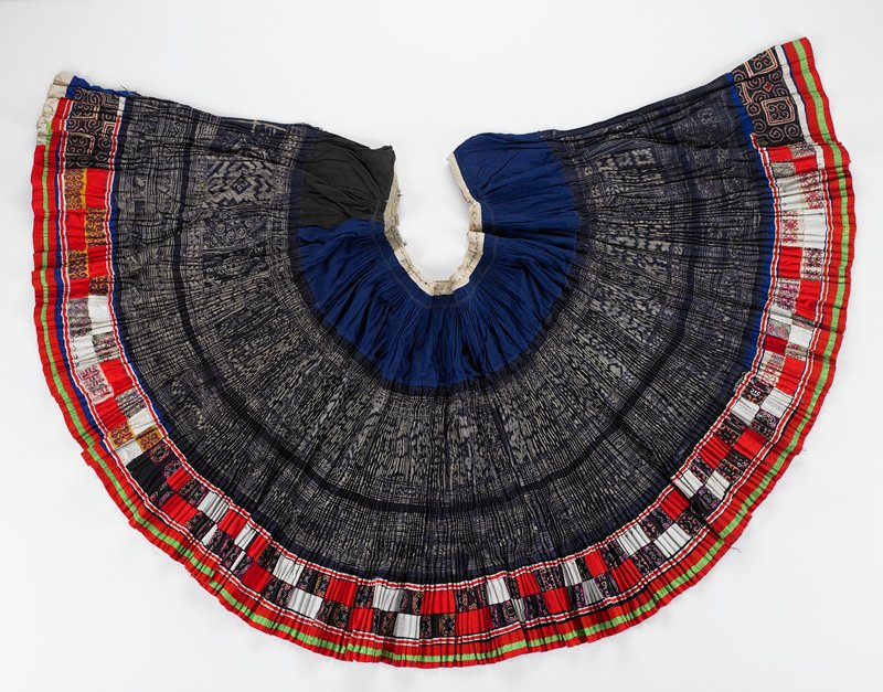 "large, pleated skirt with narrow beige waistband and ties, in three horizontal sections; top blue band (6-1/4""); center band (13"") of blue and beige geometric batik; lower, colorful (5-1/2"") band of embroidery, alternating with red and black rectangles; bottom horizontal border in red and green"