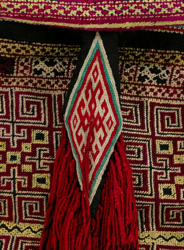 overall embroidery in red, yellow and green on dark blue; three double tassels in long untwisted red yarn hang over lower part of carrier; all lined