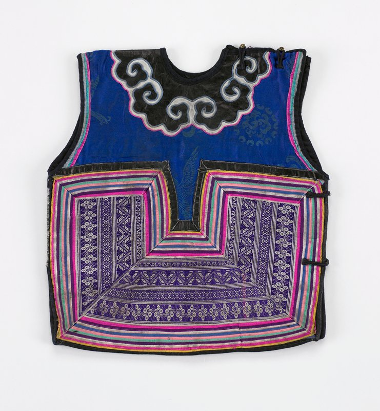 openings on PL shoulder and side fastened by brass ball buttons; front and back have same overall pattern of narrow applique color bands of pink, green, yellow, white, framing purple and white commercial embroidered tape; bib top has scrolled applique on black indigo on blue silk damask; black lining