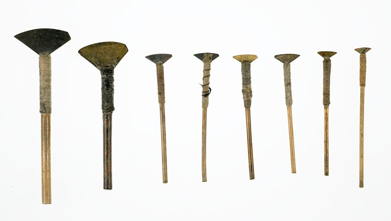 small triangular blade with one pointed corner and one rounded corner; bamboo handle wrapped with string and attached to blade