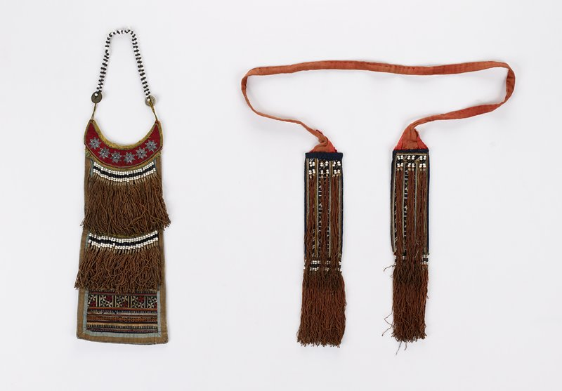 double strap of white and black beads, embellished with coins; top of panel is red with metal stars on front; fully embroidered on front with brown tassels and black and white beads; partially embroidered on back; blue main panel