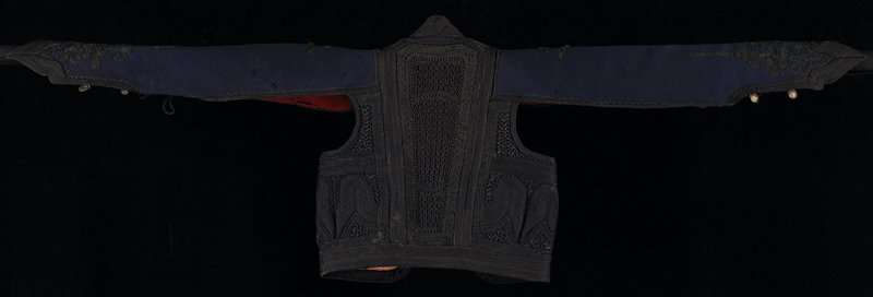 blue wool jacket with bat wing sleeves; red wool lining with paper interface, braid tape and two inside pockets; balck heavy braid and coil embroidery over entire vest; decorative buttons on lower sleeve and shoulders; large loops on sleeve side edges; probably military