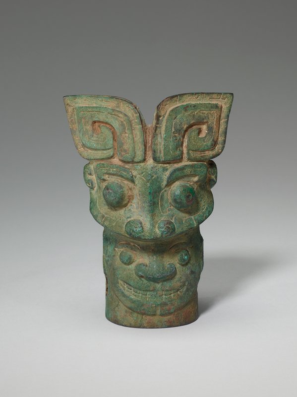 An eccentric combination of four masks occurs on this bronze. A forceful t'ao-t'ieh head with recumbent C-shaped horns, the borders decorated with straight and T-shaped scores, appears on one side of the top. This monster bites on a human head with the broad nose typical of many early masks. On the other side a ram's head, with horns turned down, bites on a head resembling a t'ao-t'ieh but with a raised elephant's trunk instead of the usual ridge in the central line. This remarkable and unusual piece is a powerful example of early Chinese sculpture. Patina green.