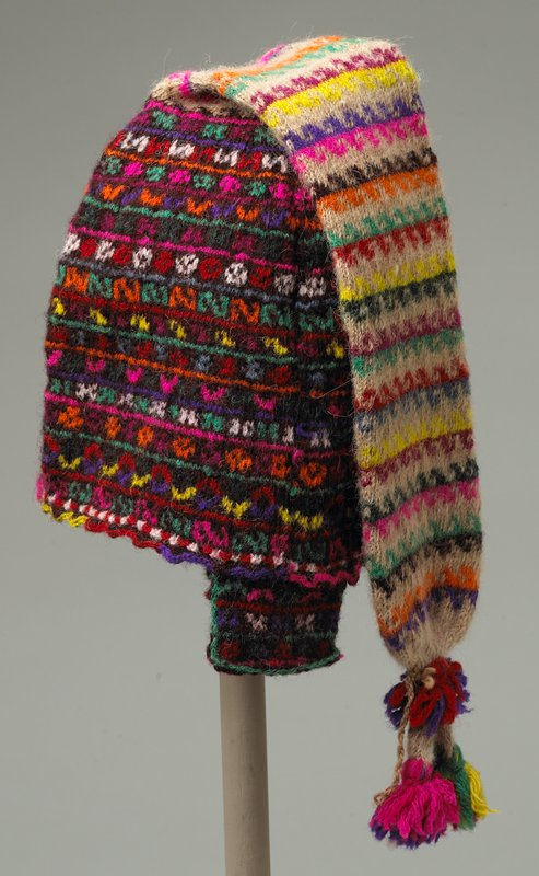 knit; bonnet part has multicolored motifs on brown; tail is light tan with multicolored motifs; two tassels at end of the tail; two short side flaps