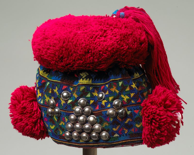 body of hat is fully embroidered in cross stitch and lined; greens, reds, yellow, blue, brown; trimmed with silver metal on front and bottom edge; two red side pompoms and large top pompom with two tassels and beads