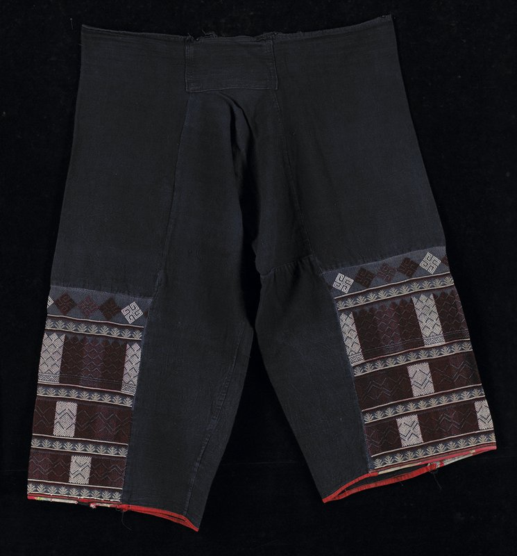dark blue with geometric embroidery on lower half of legs; crotch gusset; embroidery is burgundy and white; printed red piping on leg bottoms