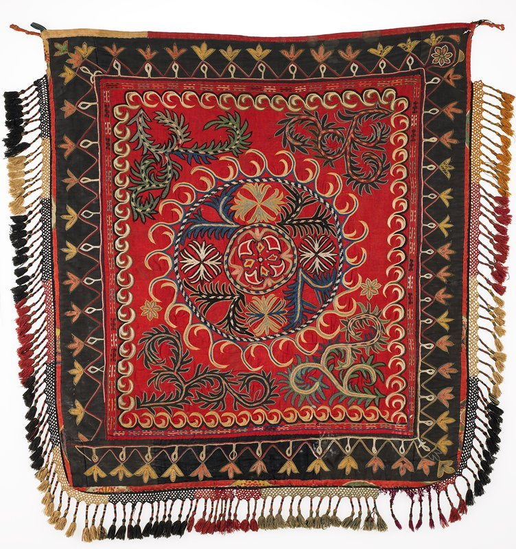 All cotton ground, pieced with a red center and black borders. Polychrome silk embroidery. The edges are bound in several different solid and printed cotton fabrics. There is a braided cotton fringe with wrapped tassels in cotton and metallic threads. Hanging tabs are present. On the reverse, there is a black and white 'ikat' printed cotton fabric and red printed cotton edging. Applied braided fringe and tassels are in sections of different lengths and colors; red, black, gold, and tan.