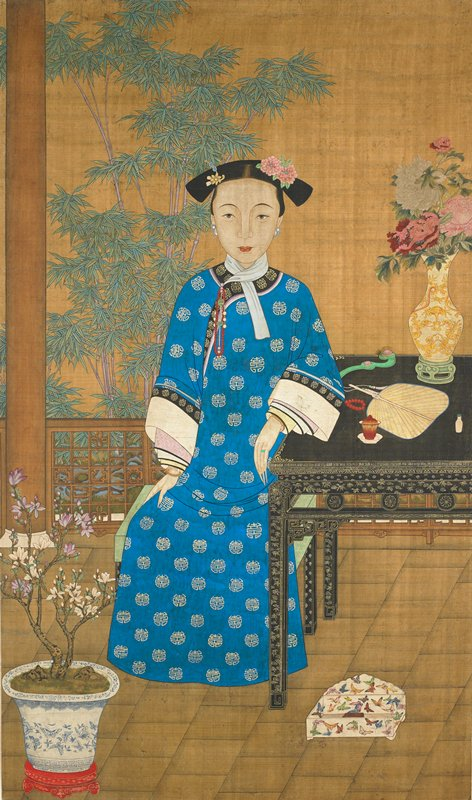 young Manchu woman seated by a lacquer table on a garden terrace with bamboo growing at L; woman wears blue robe with Shou characters and has stylish hairdo decorated with flowers and jewels; on the table are a snuff bottle, a fan, a ju-i scepter and a vase of peonies; blue and white vessel with plant LLC; butterfly-covered box on floor beside table