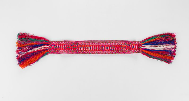 red woven sash with colors red, blue, orange and green with thick fringe of the same colors at both ends