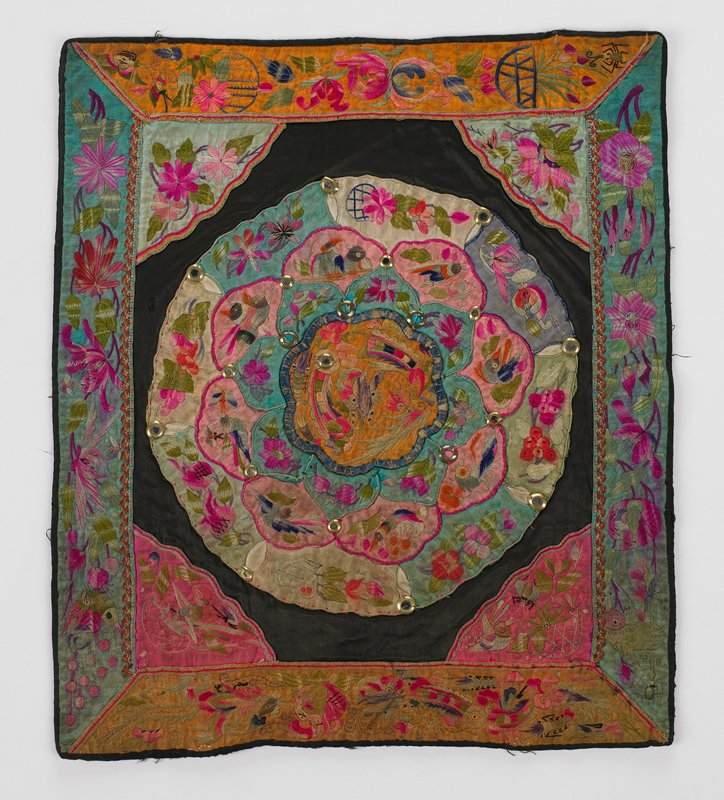 """black silk (or cotton sateen?) has elaborate appliqued circular center of pink, blue, green and gold embroidery of birds and flowers with 20 metal """"mirrors"""" at focal points of each applique; borders and corners triangles are same motif and color; black lining (linen?)"""