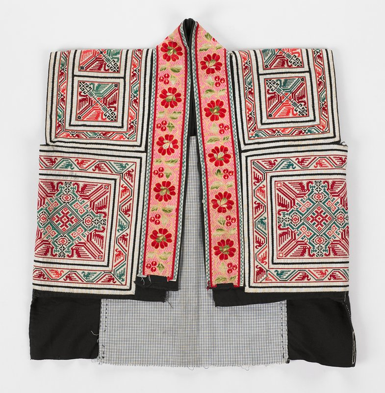 """abstract cross stitch patterns in red and green on white on square and rectangles covering vest; open front framed with 1-1/2"""" commerical silk floral tape in pink and red; lined in white and blue check and black"""