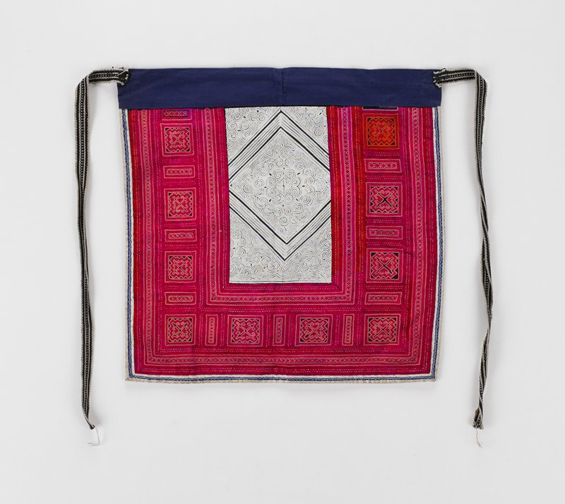 lined in dark blue with blue front band and two woven black and white ties; center blue and white rectangular batik insert surrounded on three sides by embroidery in shade of red; surrounding that is narrow blue and white border