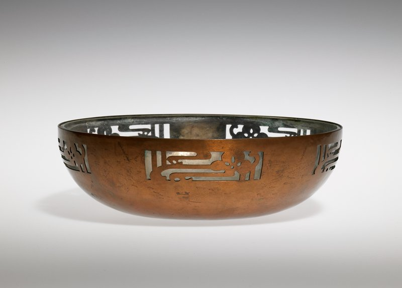 hammered copper with five cutout panels of stylized blossoms; clear glass liner (affixed to bowl)