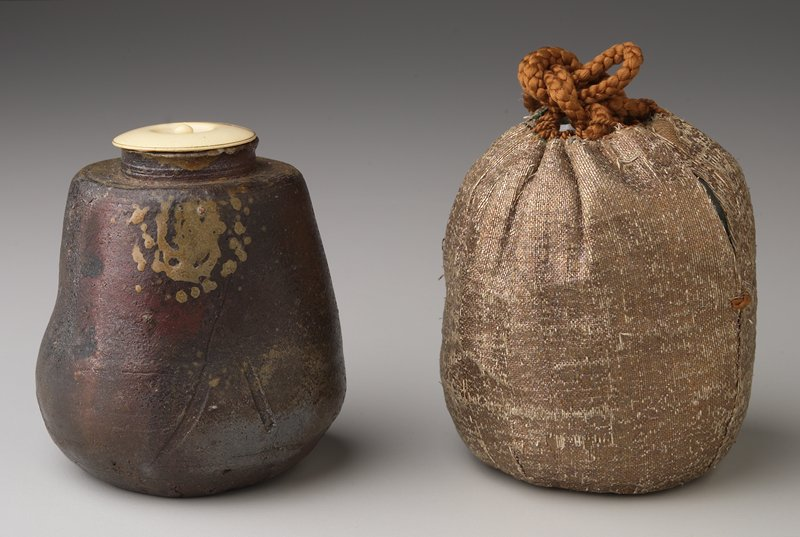 small irregularly gourd-shaped ceramic vessel; goma splash glaze; concave bottom; brown glaze with rust and gold areas; ivory lid lined with gold leaf; has storage box
