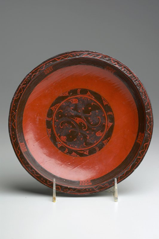 shallow dish with small flat rim; painted orange and brown; central organic scrolling design; brown rim with orange dots and zigzags; character(?) repeated 5 times around rim, 3 times on bottom