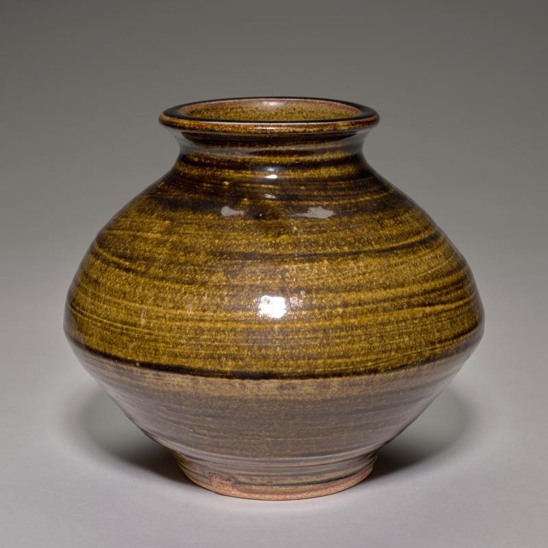 vessel flares out at center and inward; wide mouth with flat, outward-flaring mouth rim; brown-green glaze