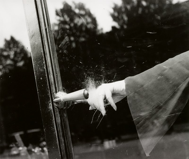 woman's hand holding a door handle behind scratched glass