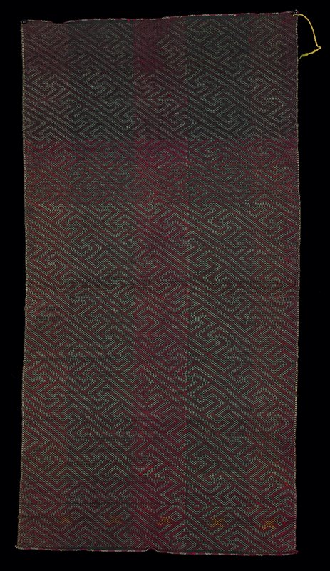 red, green, black on red and black warp; face: red and green intersecting geometric shapes; reverse: wide, red and black vertical stripes; yellow warp on both selvedges; some yellow woven crosses (face, same design) near one end; both ends neatly finished