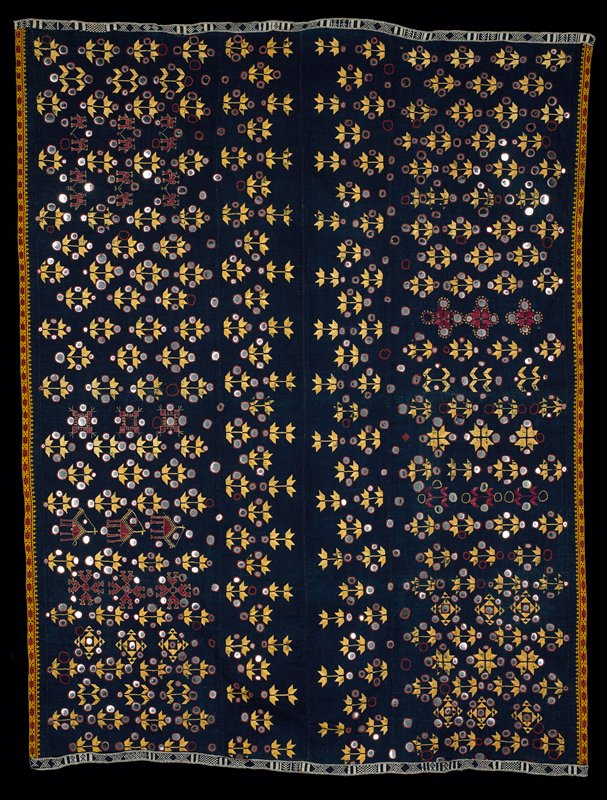 large coarse cotton navy blue three-panel rectangle with overlapping horizontal rows of silk embroidered figures incorporating circular metal mirrors; some figures appear to be animals; embroidery is gold and red; blue and white woven geometric pattern braid on right and left sides; gold and red border pattern embroidered on top and bottom