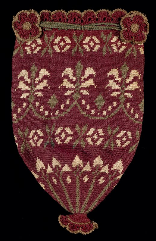very tightly crocheted conical shape; no closure; wine colored background with floral patterns in green and ecru; bottom and upper sides have floral ornaments; scalloped top edge