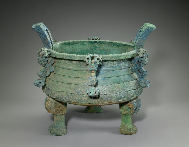 "green patina overall; rounded body with inward-flaring shoulder and outward-flaring flat mouth; three feet; six decorative brackets; two ""handles""; elaborate decorations overall of geometric forms"