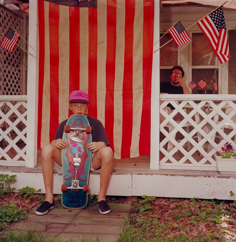 boy wearing a pink cap, blue shirt and black slip-on tennis shoes, resting his chin against a skateboard held in front of him; boy is seated at the edge of a porch in front of a large U.S. flag; man with beard and glasses seated on porch at right