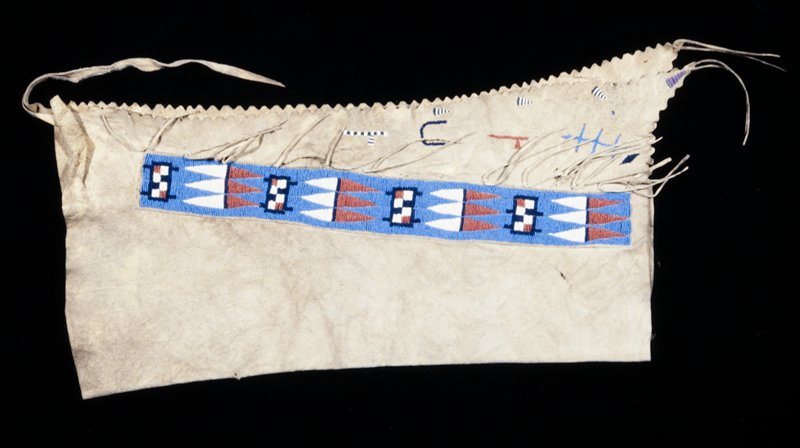 pair of leggings, beaded buckskin; applique beadwork in geometric pattern in red, white and blue down sides of chaps