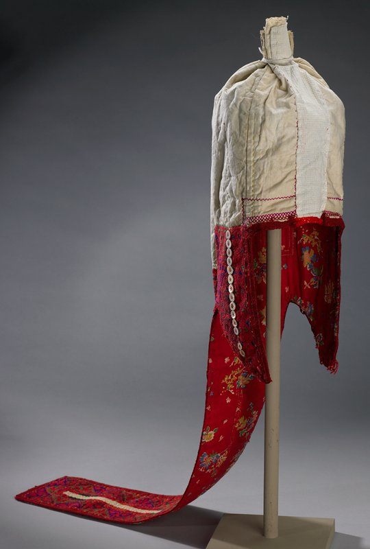 "red; natural muslin and other cotton strips seamed and gathered at top to form cap; ear flaps and long strip down back; some cross stitching on cap front; lined in red floral print cotton; vertical row of 3/8"" flat pearl buttons down center of both ear flaps (some two hole, some four hole); heavy chain stitch embroidery on ear flaps and long back strip; floral diamond shapes, swirls and chain stitch edging; designs are red with blue and green outlining; very center of back strip muslin has yellow straight stitch embroidery sewn on trim"