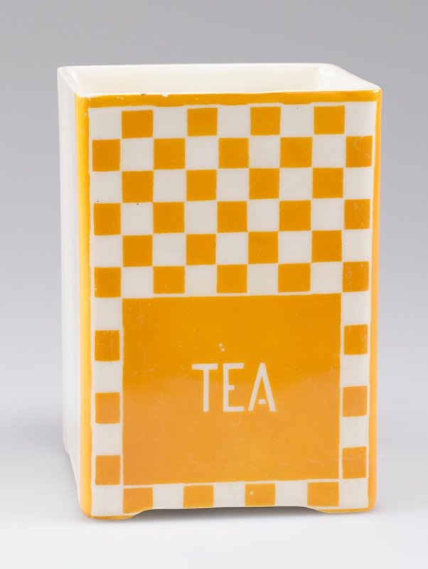 "open square container; porcelain with one side decorated with yellow-orange and white checkerboard and ""TEA"" in white"
