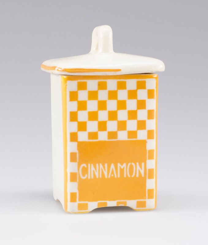 "small square container with cover with small handle; white porcelain decorated with yellow-orange checkerboard and ""CINNAMON"" in white on front; stripe around edge of cover on front and sides"