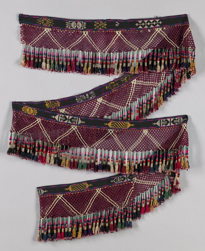 black, maroon and white band of tassels with supplementary weft of yellow and white designs; maroon and white open braid with hanging tassels wrapped in red, green and black with metal beads, pink seed beads and metal wrapped cord; end cords (two-ply, twisted) are same color fringe in each bundle but all bundles are not same color; random placement of yellow, maroon, green, blue and red; all end in pink bead