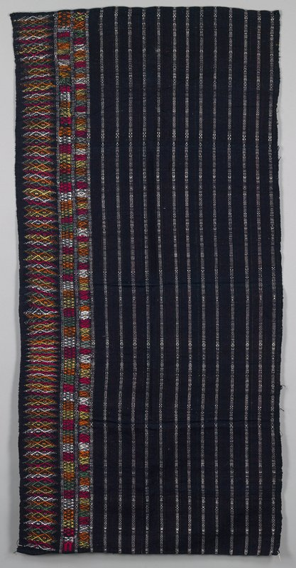 dark blue and white vertical stripes in plain weave with two narrow and one wide multicolor supplemental bands at one edge in green, red, white, yellow and orange; hemmed ends