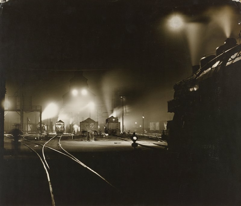 train yard with cars and engines in middle ground at L; shadowy engine at R edge; night scene with lights