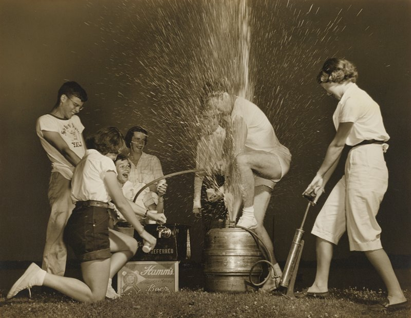 man in shorts tapping a beer keg, which is spraying; woman at R wearing pedal pushers operates pump; three women and one man at L; another figure behind man tapping keg